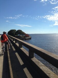 biker leaning on rail overlooking the water